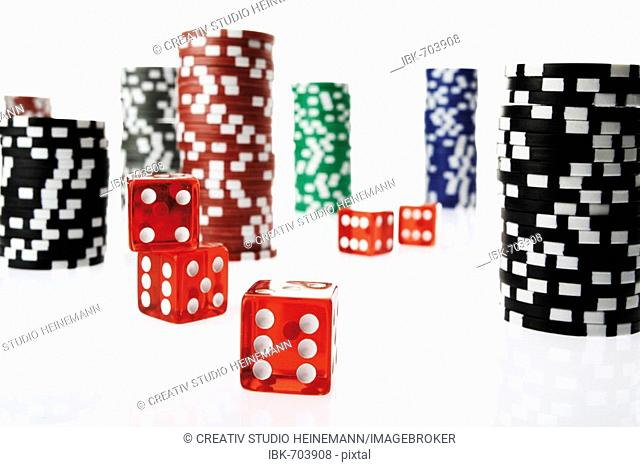 Stacked poker chips and red die