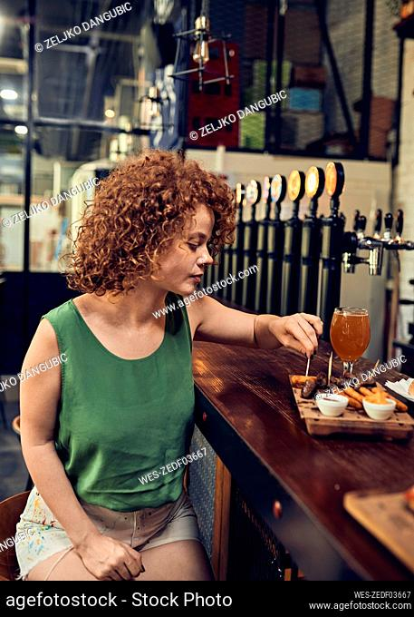 Woman having tapas at the counter in a pub