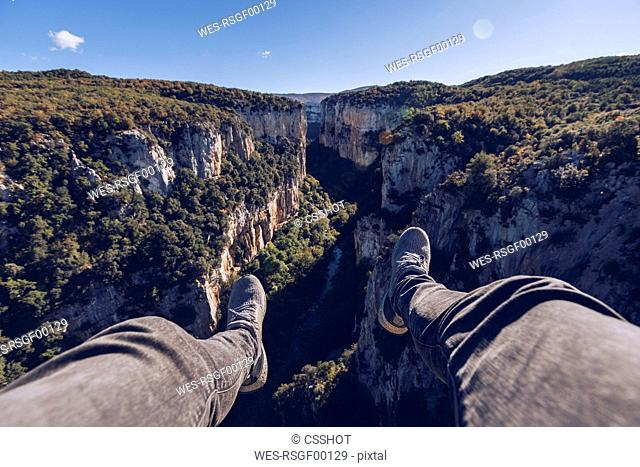 Spain, Navarra, Irati Forest, man's legs dangling above landscape with gorge