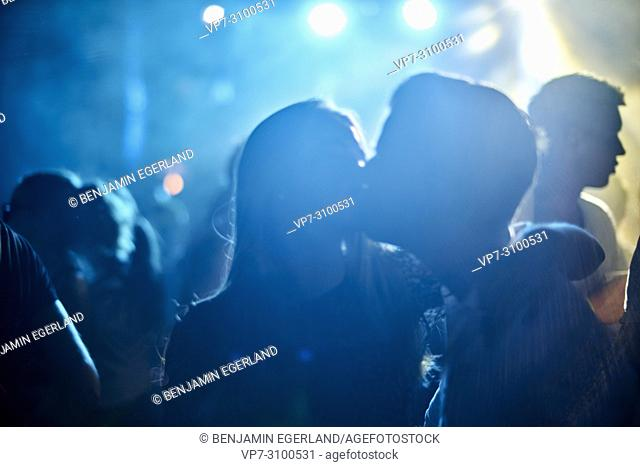 unidentifiable silhouettes of lovers kissing at music festival