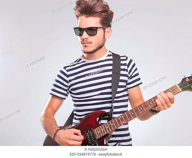 portrait of young man playing at electric guitar in studio background while looking away