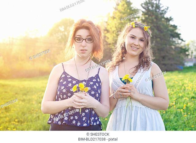 Caucasian women holding flowers in field