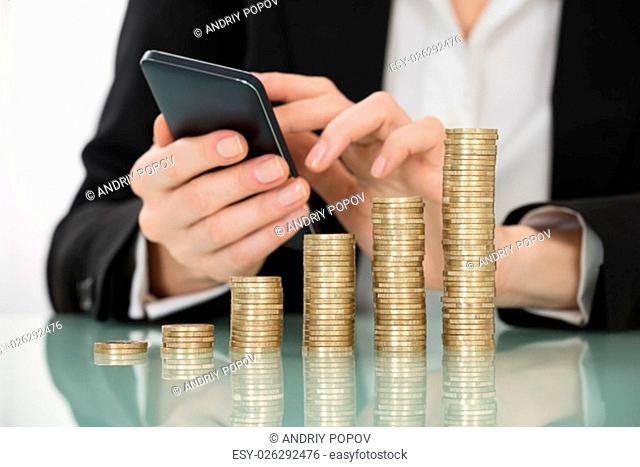 Close-up Of Businesswoman Using Smartphone With Stacked Coins On Desk