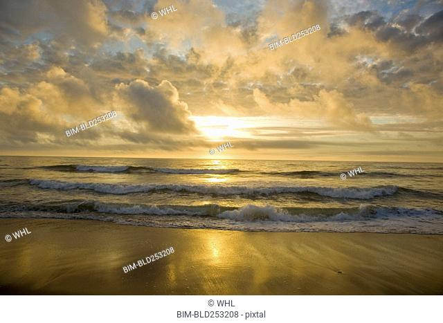 Ocean waves on beach at sunset