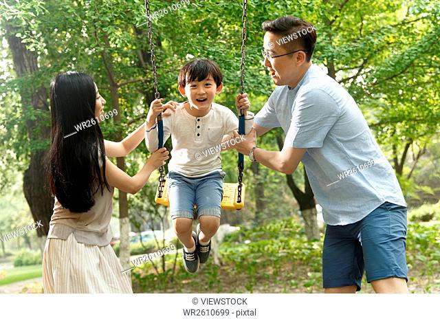 Happy family of three swing