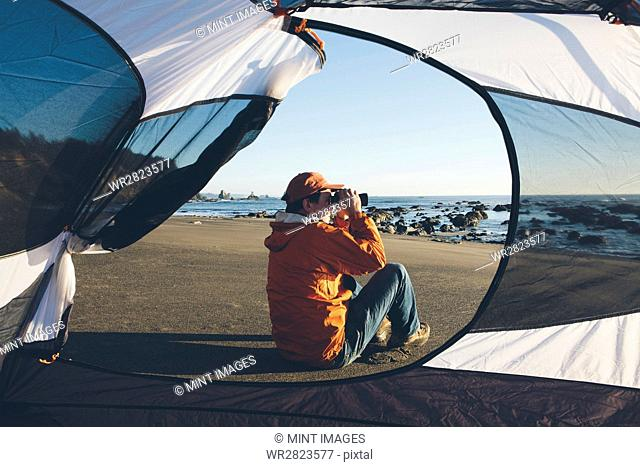 Man framed by camping tent, sitting on beach and looking through binoculars at dusk, Olympic National Park, Washington, USA