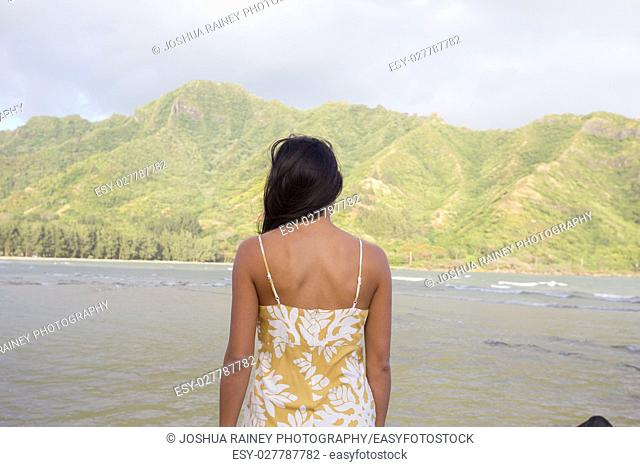 Lifestyle portrait of an attractive Hawaiian woman wearing a flower dress at Kahana Bay on Oahu Hawaii