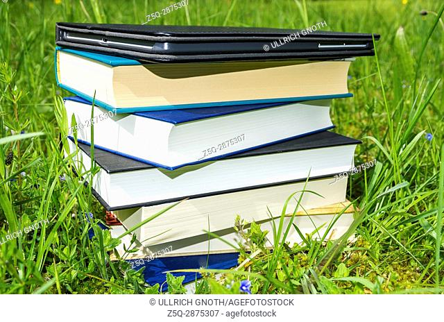 Pile of various books plus tablet in the fresh green grass
