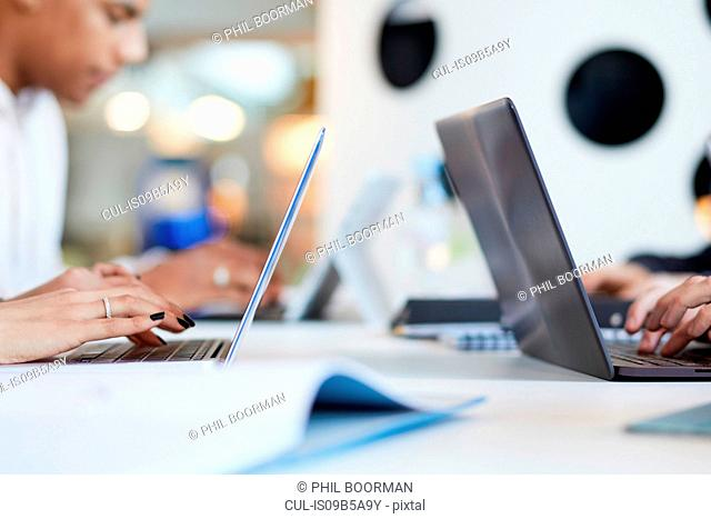 University students using laptops and digital tablet, working together