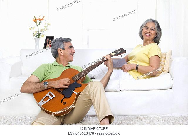 Husband playing the guitar while wife is listening