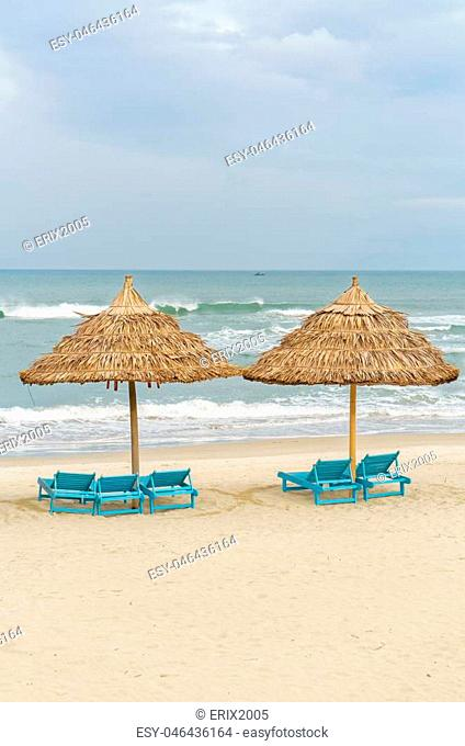Palm shelters and sun beds in the China Beach in Da Nang, Vietnam. It is also called Non Nuoc Beach. South China Sea on the background