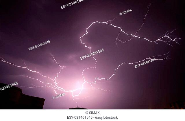 Thunder storm and lightning above the town buildings