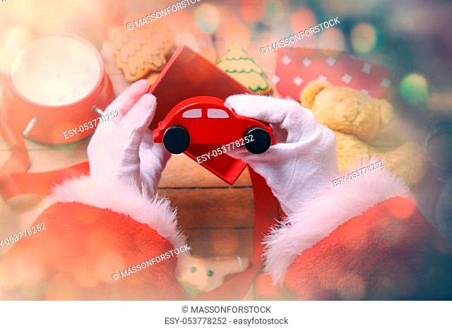 Santa Claus have wrapping a Christmas toy car and other gifts on wooden background