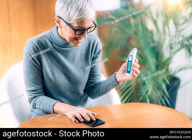 Senior woman recording body temperature with non-contact digital thermometer, using smart phone app