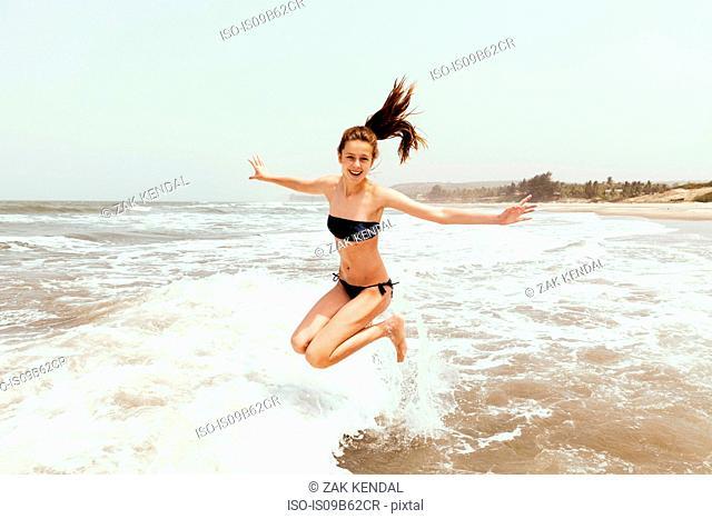 Teenage girl jumping in sea, Goa, India, Asia
