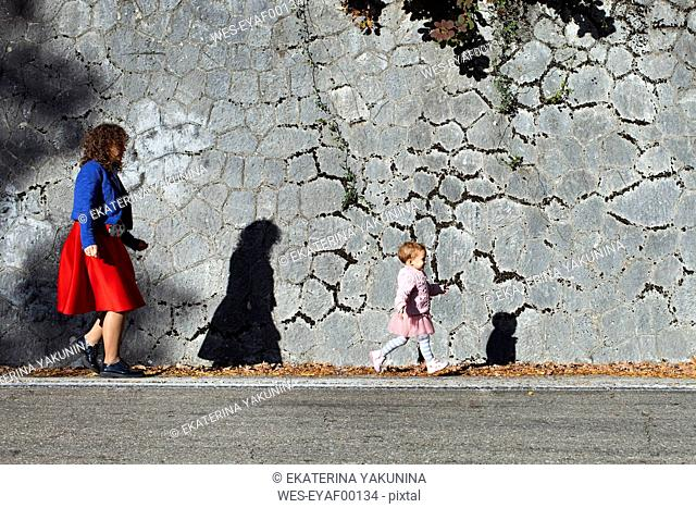 Little girl running with her mother at a stone wall
