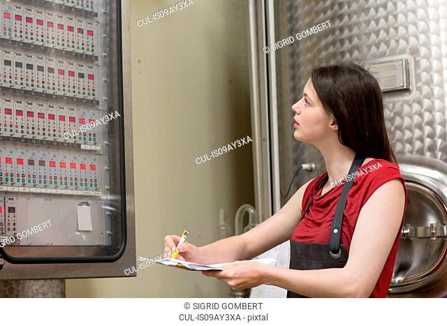 Young woman looking at control panel in wine cellar