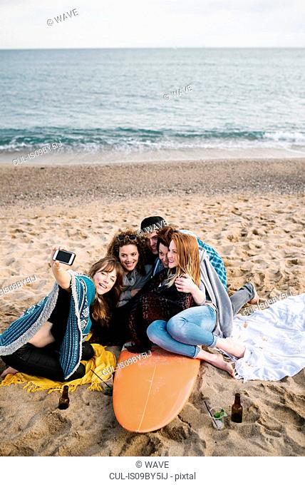 Friends taking selfie on surfboard at beach party, Barcelona, Spain