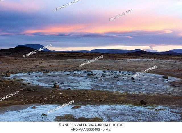 Blue coloured minerals, left behind by volcanic mud puddles and fumes, contrast with the orange coloured sky in Hveraröndor Hverir Geothermal Area at...