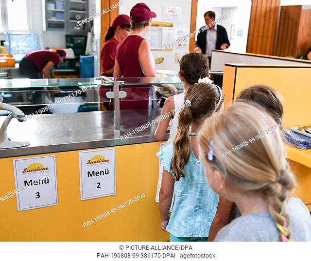07 August 2019, Berlin: Before lunch, pupils stand in the cafeteria in the primary school on the Wuhlheide in the queue in front of the food counter
