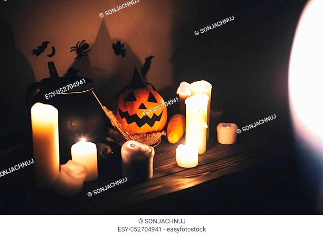 Happy Halloween. Jack o lantern pumpkin with candles, bowl, witch broom and bats, ghosts on background in dark spooky room. fall halloween image