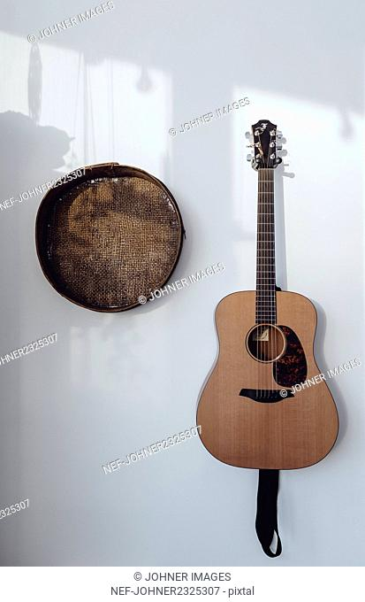 Guitar and basket hanging on wall