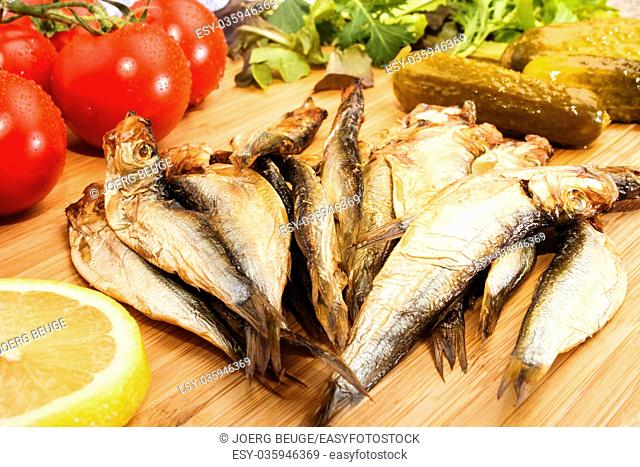 smoked sprats with salad, tomatoes, a slice of lemon and spice cucumbers on a wooden plate