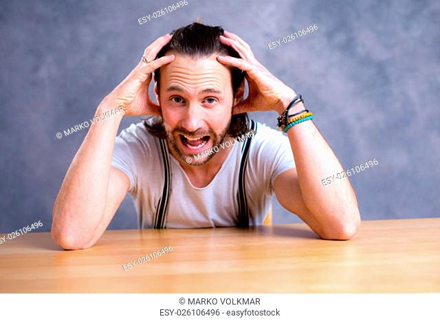 young bearded man lokking shocked in to the camera