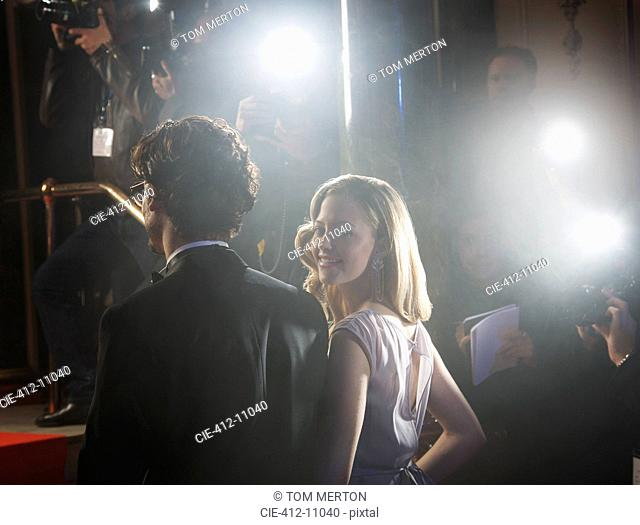 Paparazzi photographing celebrity couple at red carpet event