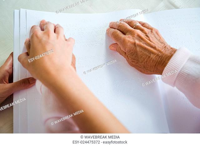 Nurse helping senior woman with braille