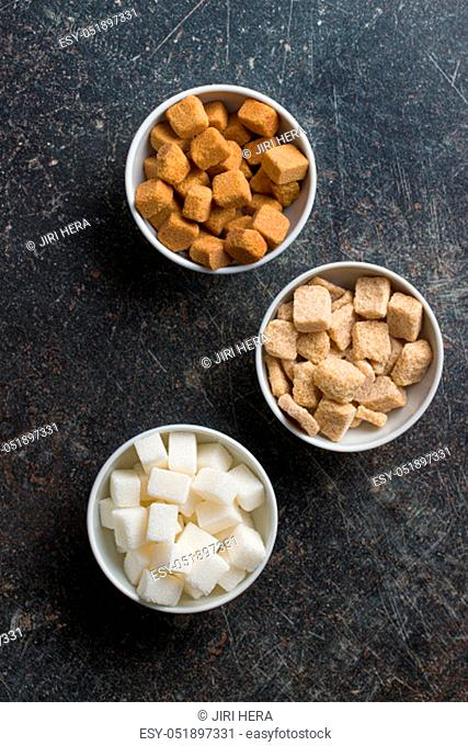White and brown sugar cubes in bowls. Top view