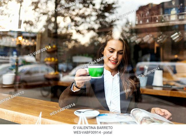 Smiling young woman in a cafe reading a magazine