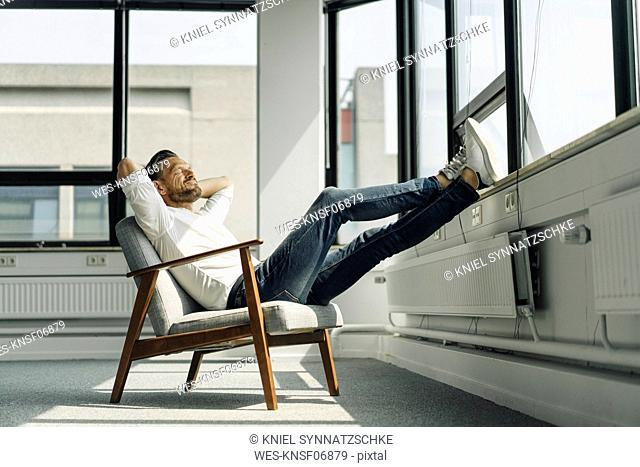 Mature businessman relaxing at the window in empty office