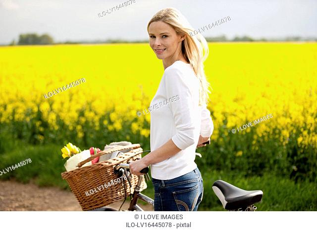 A young woman pushing a bicycle next to a rape seed field in flower