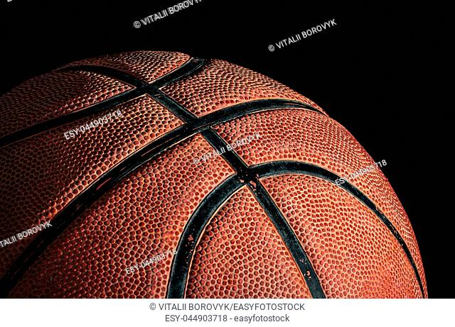 Part of basketball ball illuminated from above. On a black background. Side view