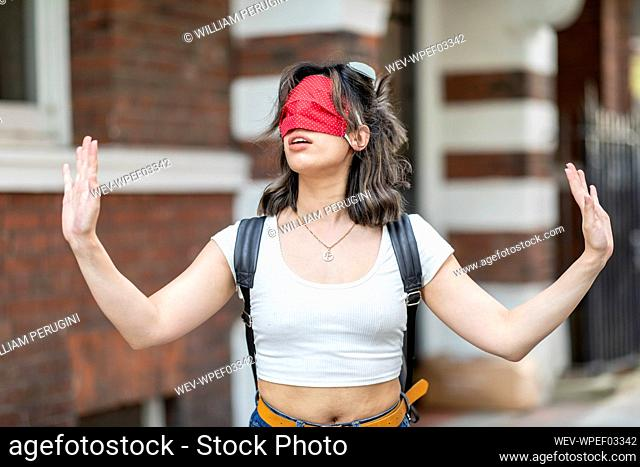 Young woman wearing red face mask on eye gesturing while standing in city