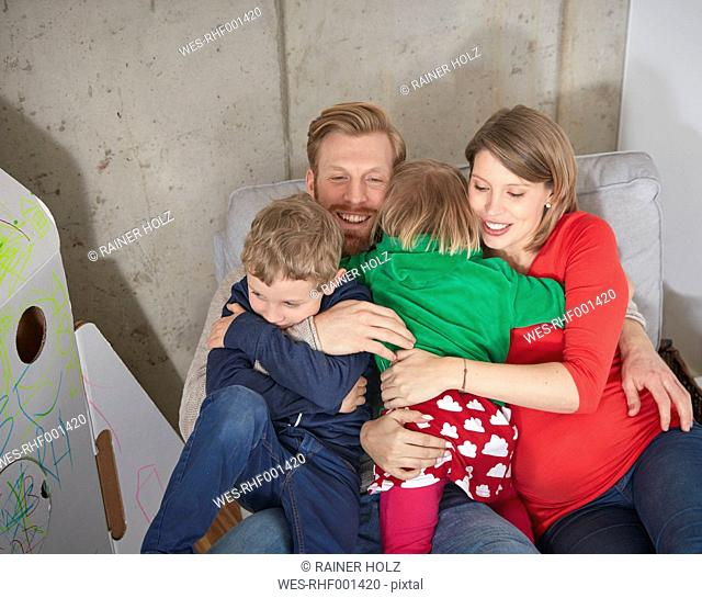 Happy family with pregnant mother cuddling