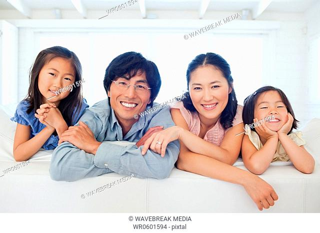 A family smiling together in the room with a window