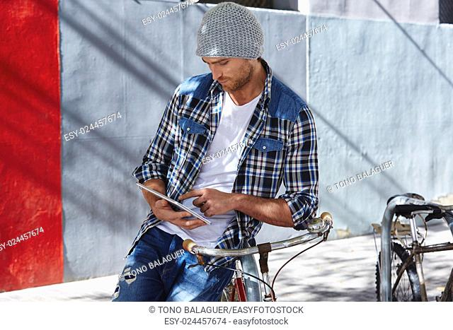 Young man using tablet pc touch in a bicycle casual clothing outdoor