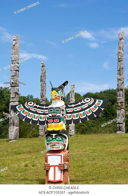 Thunderbird and Man holding copper by Bruce Alfred, older poles behind, at Namgis Burial grounds, Alert Bay, Cormorant Island, Vancouver Island