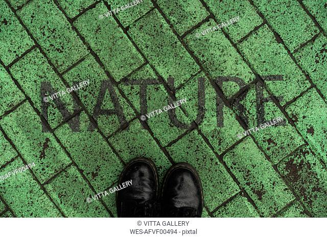 Black shoes on green pavement with stenciled word 'Nature'