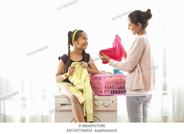 Daughter sitting on washing machine mother folding laundry