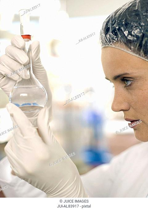 Female scientist examining liquid in conical flask