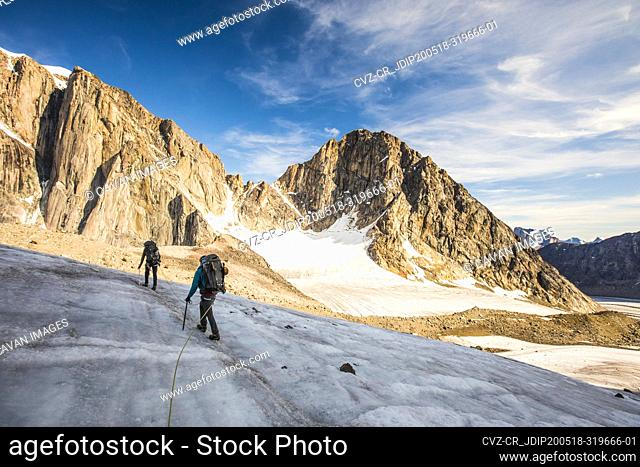 Backpackers crossing a glaciated mountain on Baffin Island