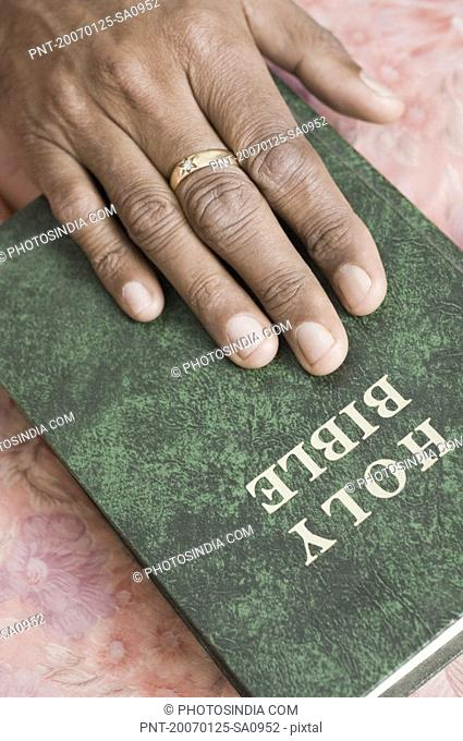 Close-up of a person''s hand on the Bible