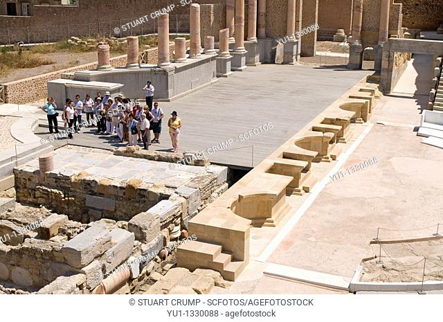 Tourist group look around the Roman Amphitheatre in Cartagena, Murcia, Spain