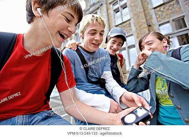 Close-up of a teenage boy listening to music with his friends beside him