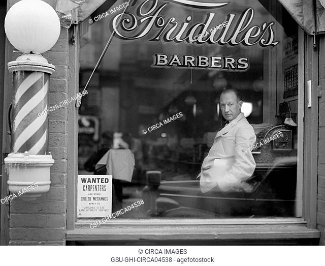 Portrait of Barber in Barber Shop Window, Help Wanted Sign Looking for Skilled Labor Resources Posted in Window by Virginia State Employment Service