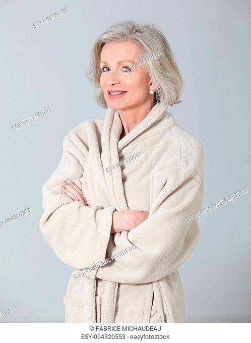Senior woman in bathrobe standing on white background