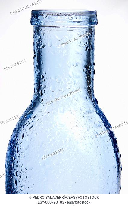 foreground of a blue glass bottle with splashes of water and white background